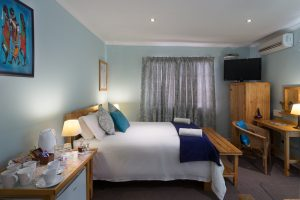 Room 6 has a double bed and two singles, with an en-suite bathroom with shower